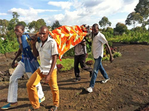 Family members carrying a sick mother to be on a makeshift stretcher.